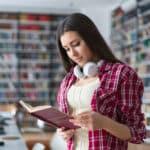 Frau liest Buch in Bibliothek