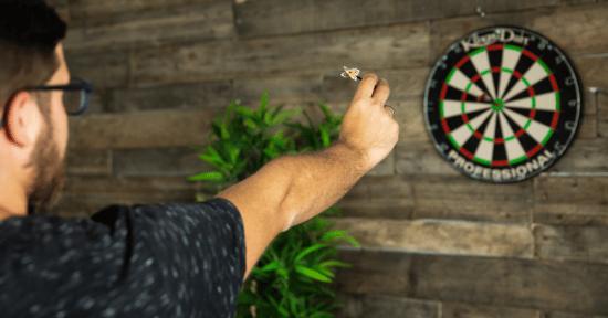 Mann wirft auf Dartscheibe: Ein Symbolbild dafür, um Ziele mit Messenger Marketing zu erreichen