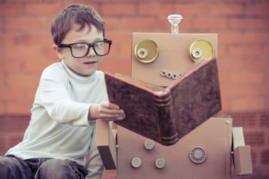 Kind hält Roboter Buch hin: Symbolbild dafür, den Chatbot für die Marketingkampagne vorzubereiten