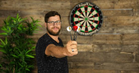 Mann spielt Dart: Ein Symbobild für die notwendige Zielgenauigkeit beim Texten