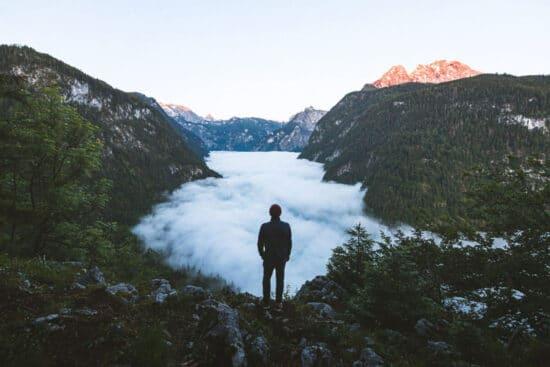 Abbildung: Mann steht in den Bergen über einem Meer aus Wolken